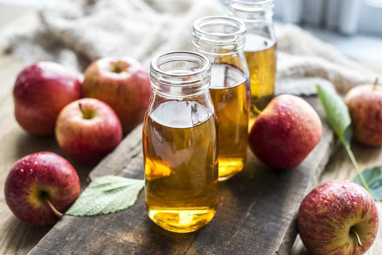 Sok Jabłkowy SZD Brzezna - propozycja podania w słoiczkach na drewnianym blacie pośród owoców jabłek.